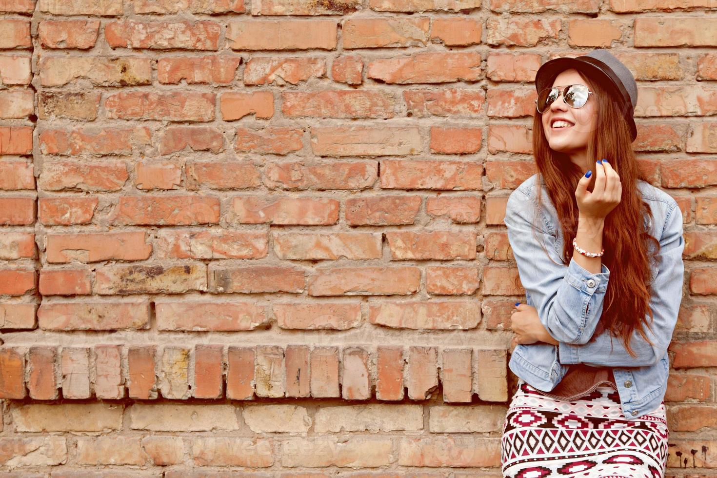 bella ragazza teenager sveglia che sorride vicino al muro di mattoni foto