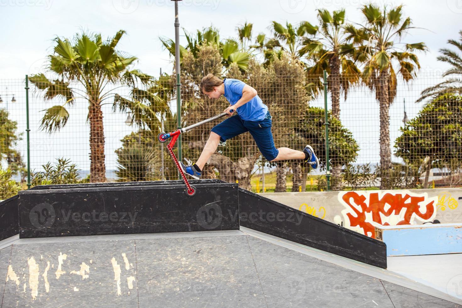 ragazzo adolescente cavalca il suo scooter al parco skate foto