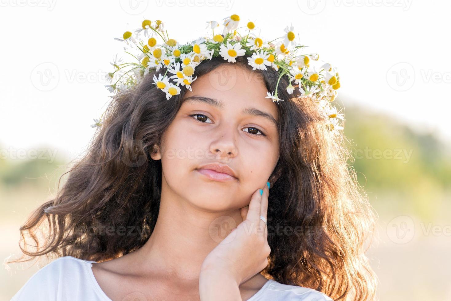 ragazza teenager con una corona di margherite in campo foto