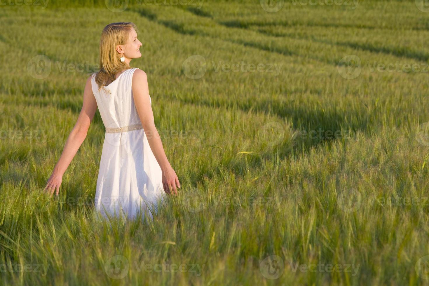 ragazza che cammina attraverso il campo dell'orzo foto