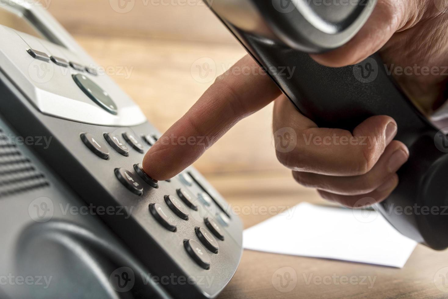 mano maschio che compone un numero di telefono foto