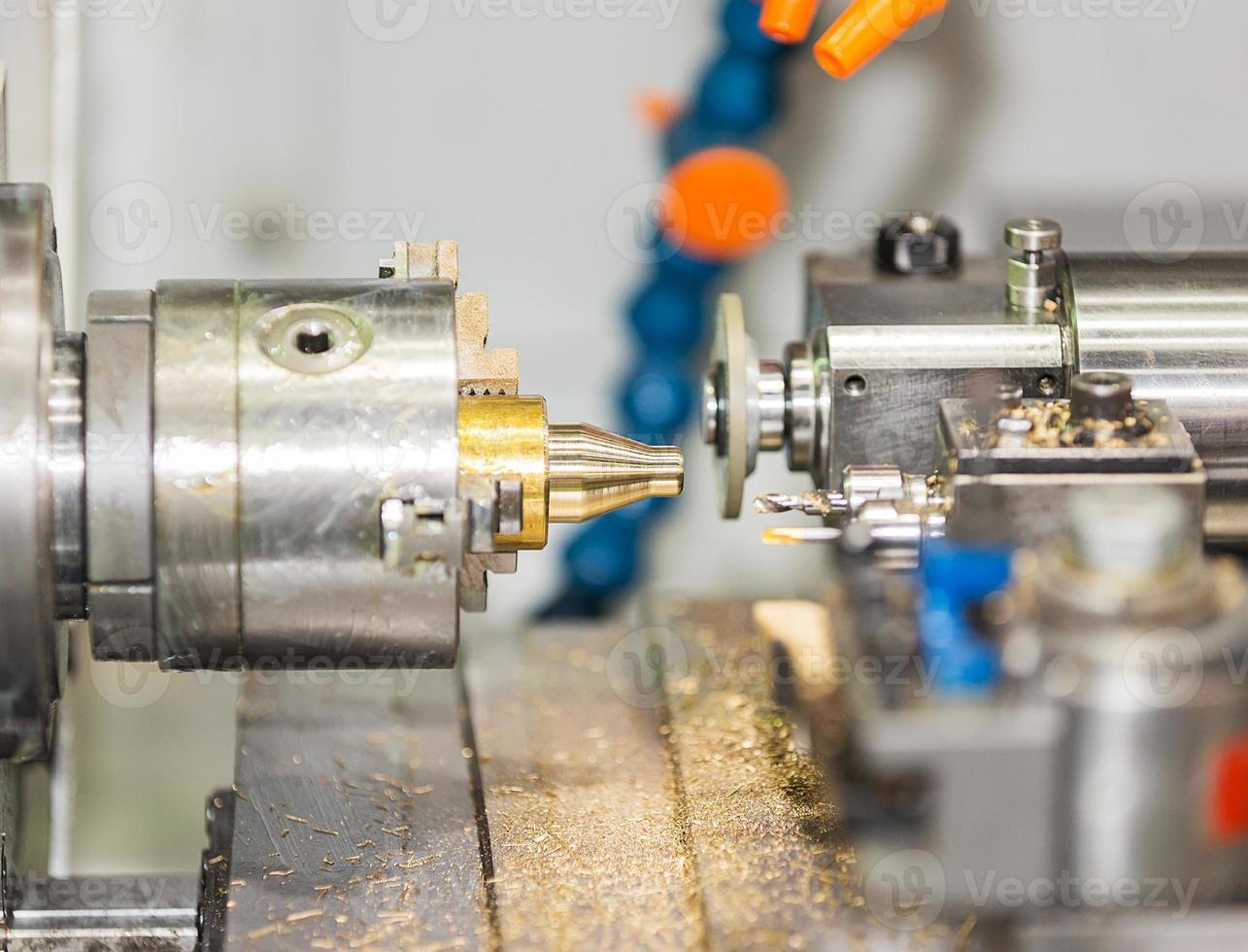 operatore che gira e macina l'autopart di ottone dal tornio di CNC foto