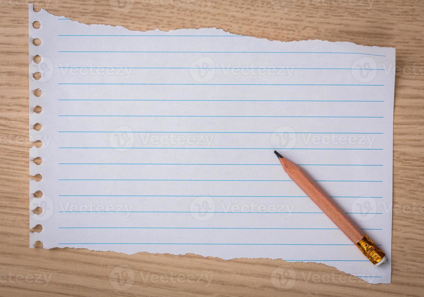 carta bianca del taccuino con la matita su uno scrittorio di legno foto
