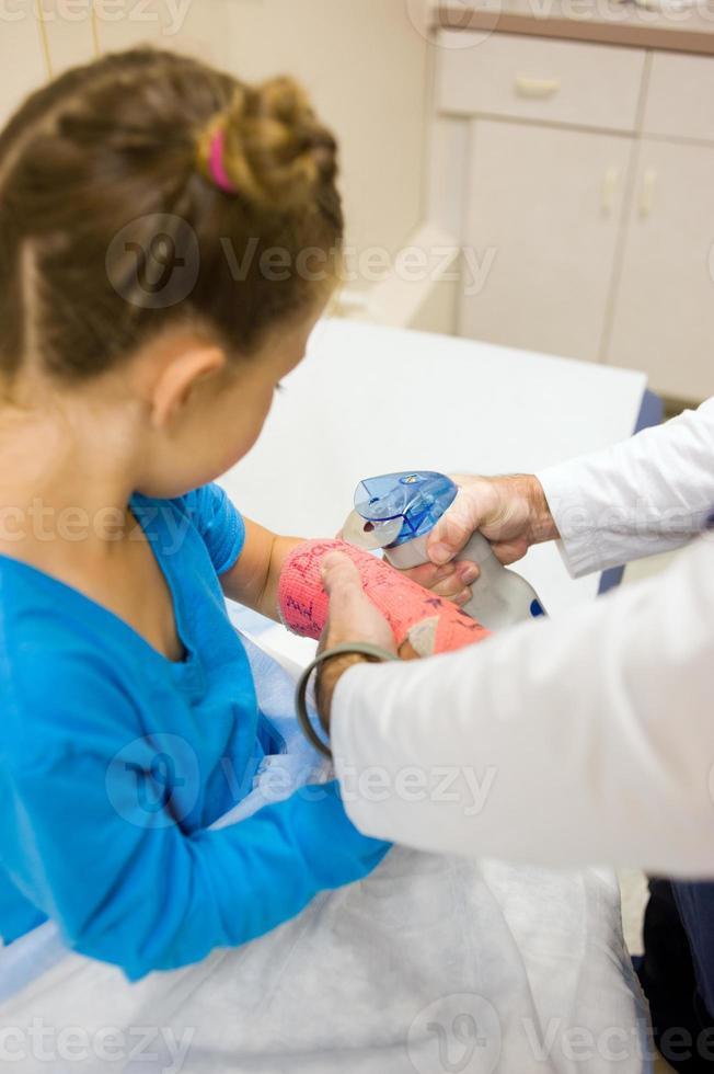la bambina osserva attentamente mentre il medico inizia a tagliare (serie) foto