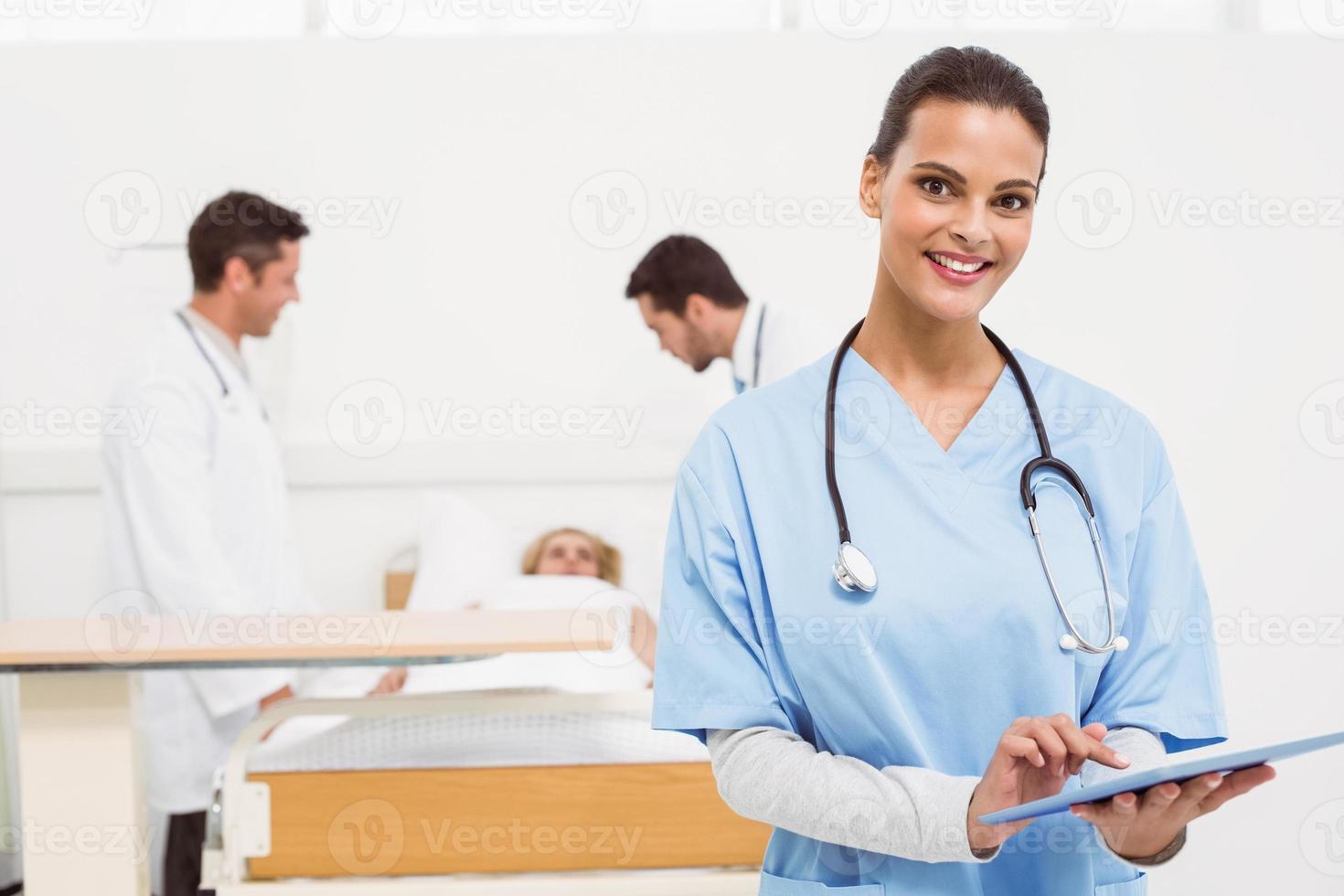 medico che per mezzo della compressa digitale con i colleghi e il paziente dietro foto