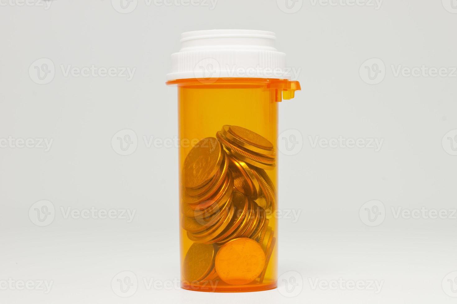 bottiglia di prescrizione sanitaria e piena di monete foto