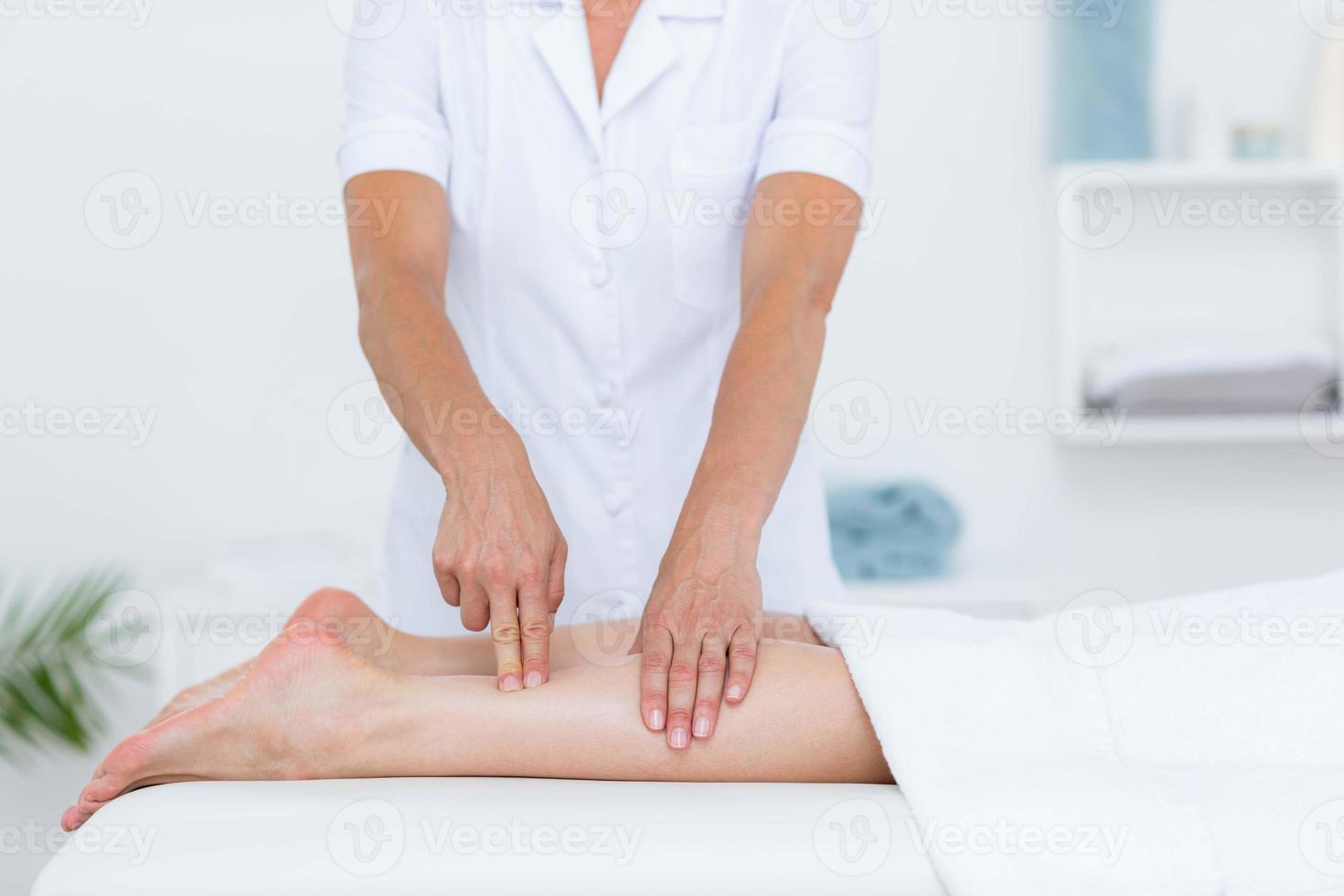 Fisioterapista che fa massaggio alle gambe foto