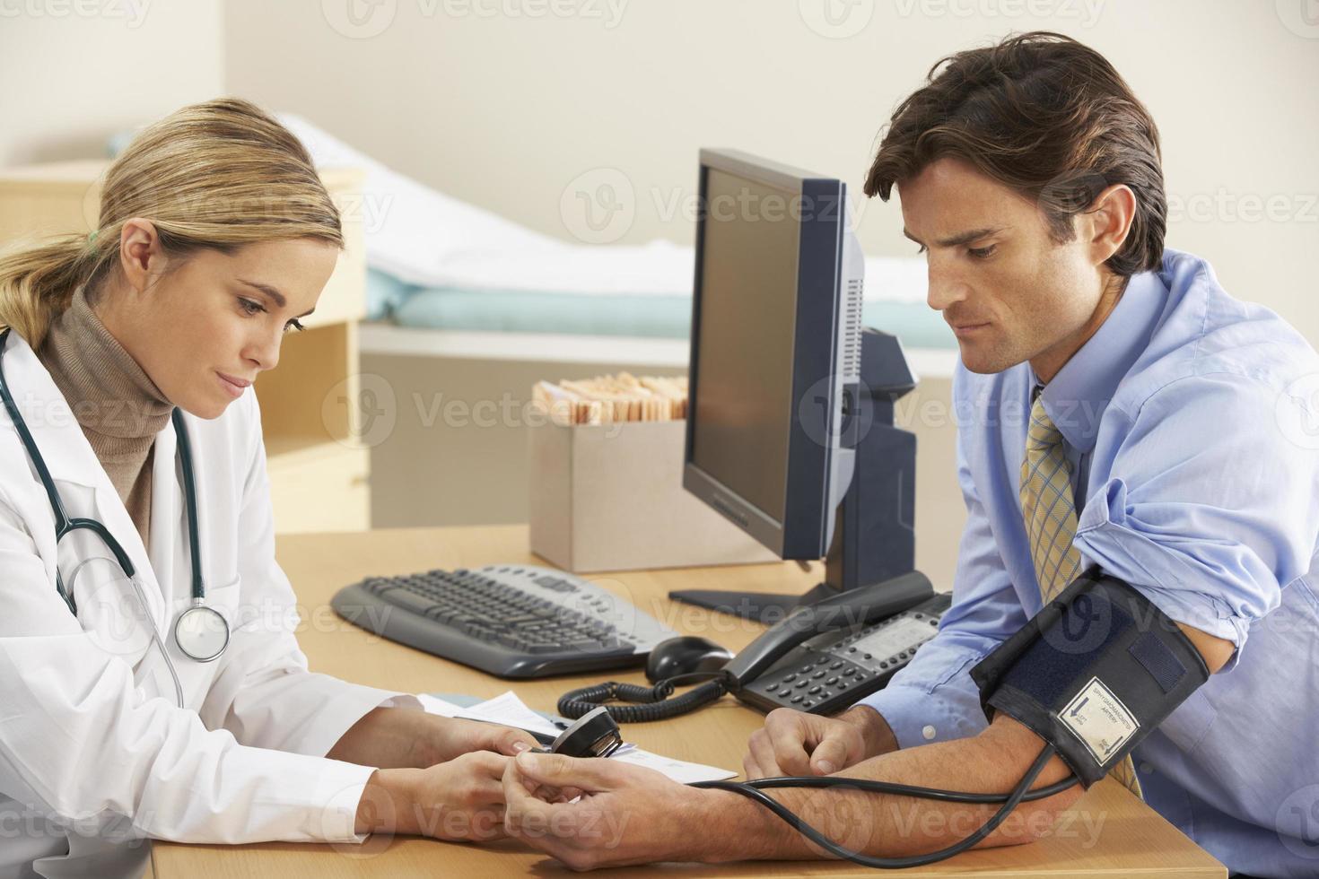 un medico che parla con un paziente e prende la sua pressione sanguigna foto
