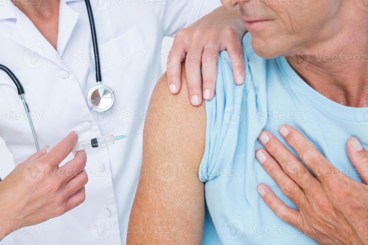 medico che fa un'iniezione al suo paziente foto
