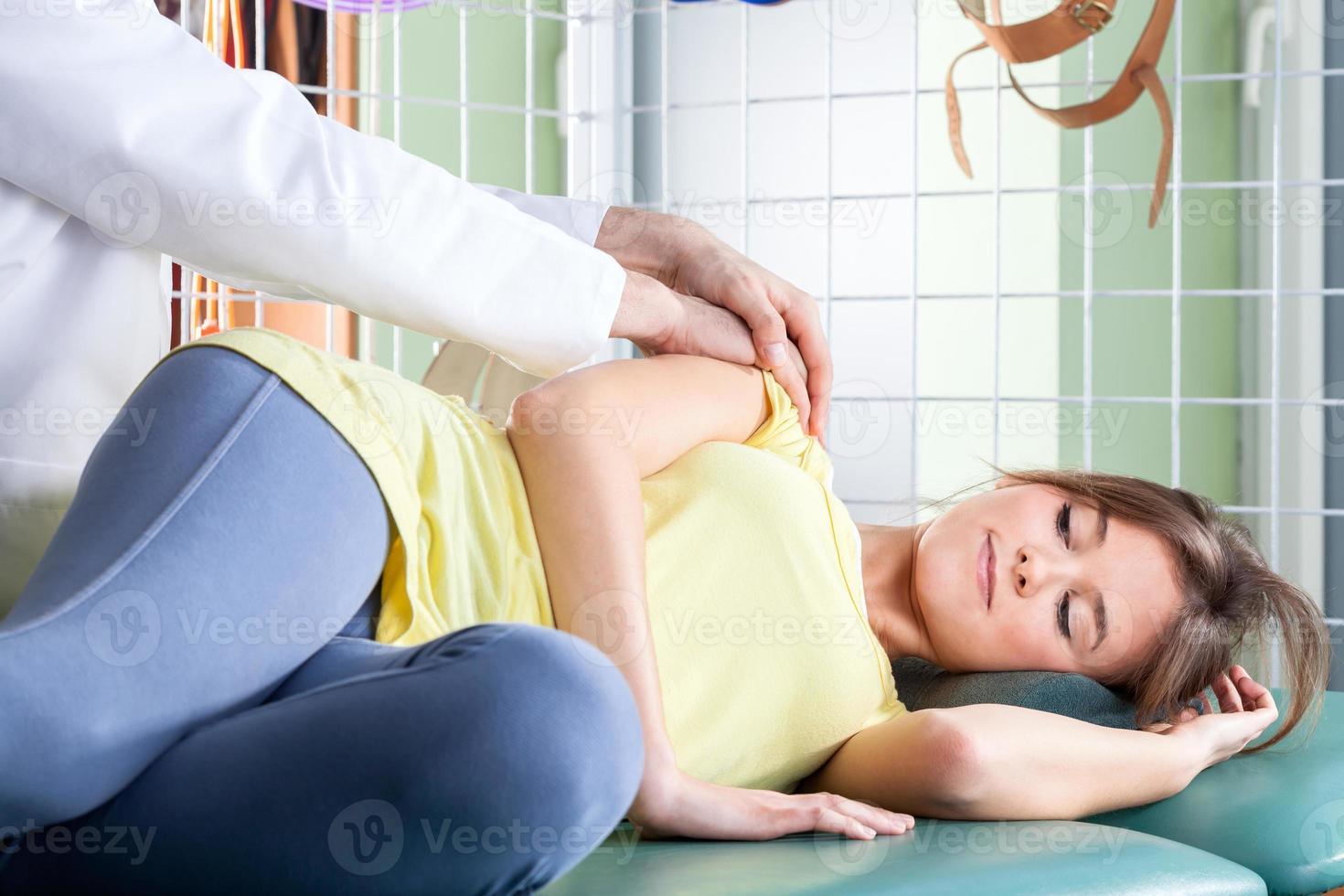 Fisioterapista che massaggia il braccio del paziente foto