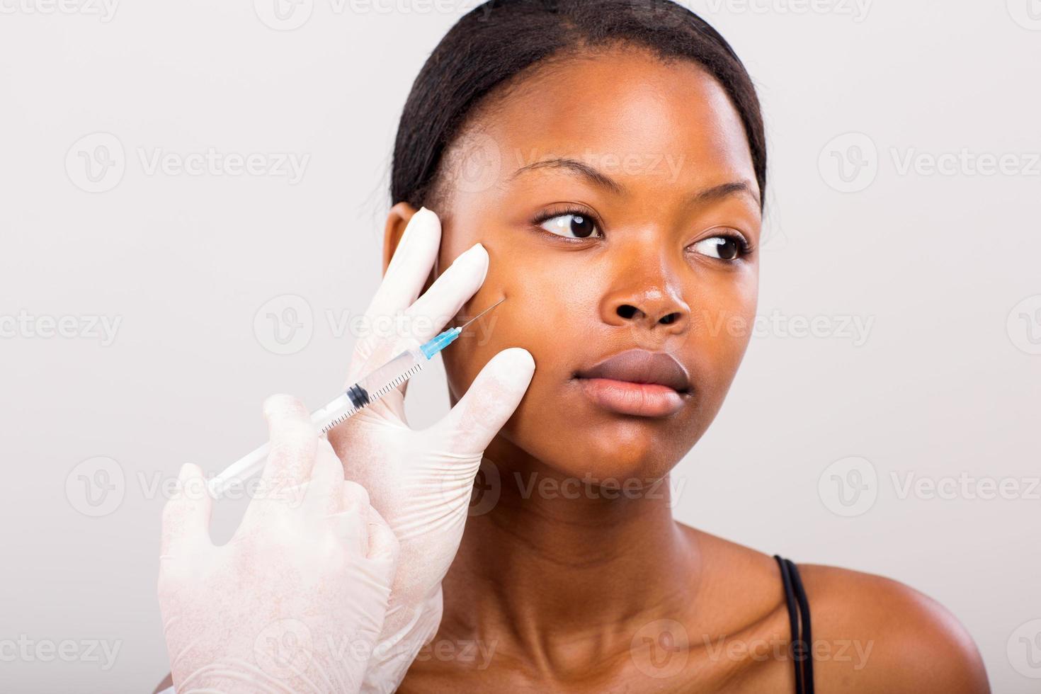 medico che fa l'iniezione di lifting facciale della giovane donna foto