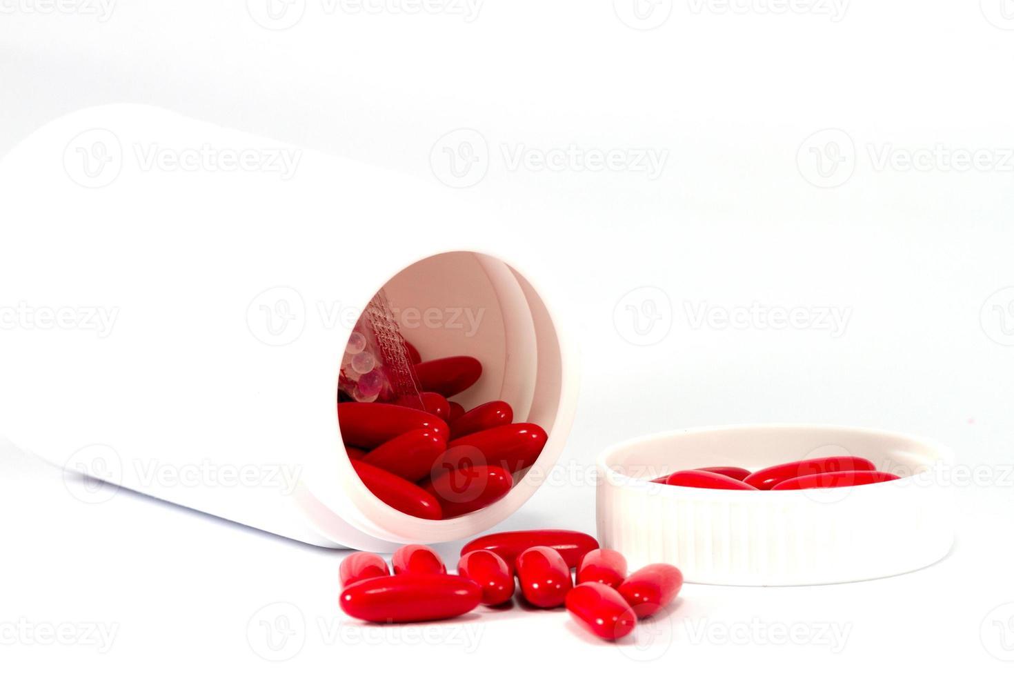 pillole rosse della medicina che versano dalla bottiglia bianca foto