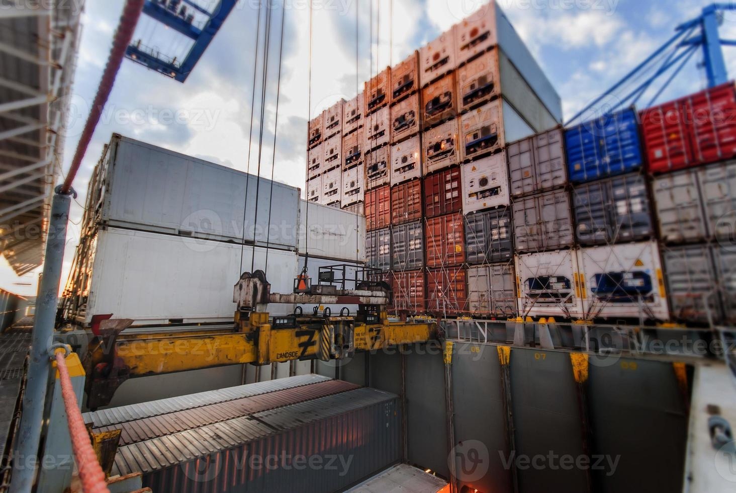 la gru portuale solleva il container durante l'operazione di carico foto