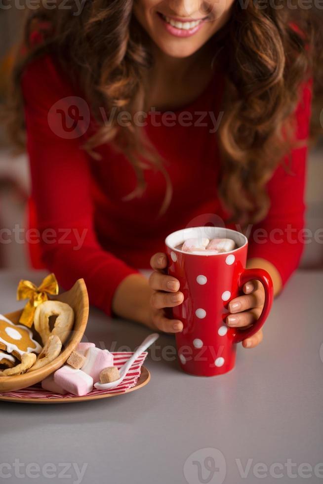 donna che mangia tazza di cioccolata calda e dolci natalizi. avvicinamento foto