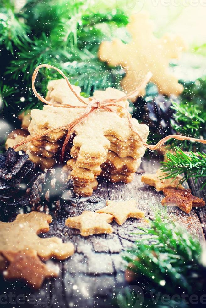 biscotti allo zenzero fiocchi di neve su fondo in legno. rustico foto