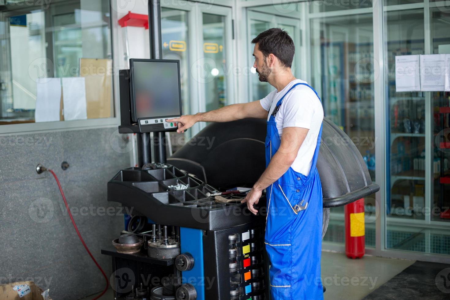 il meccanico prepara una macchina dell'equilibrio foto