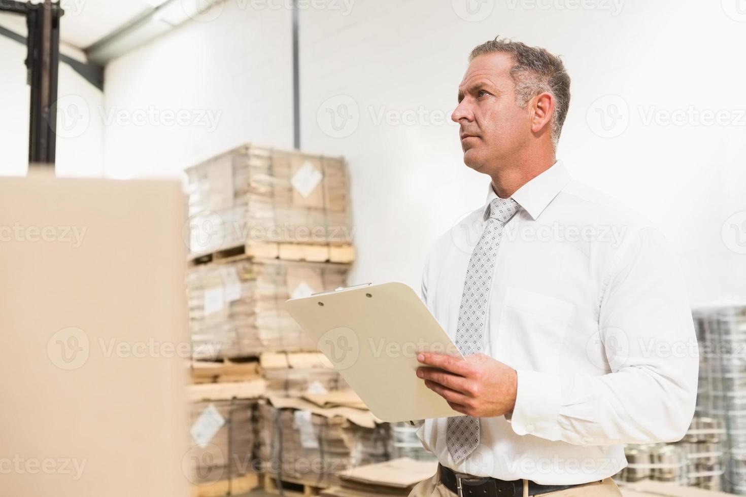 responsabile del magazzino che controlla la sua lista negli appunti foto