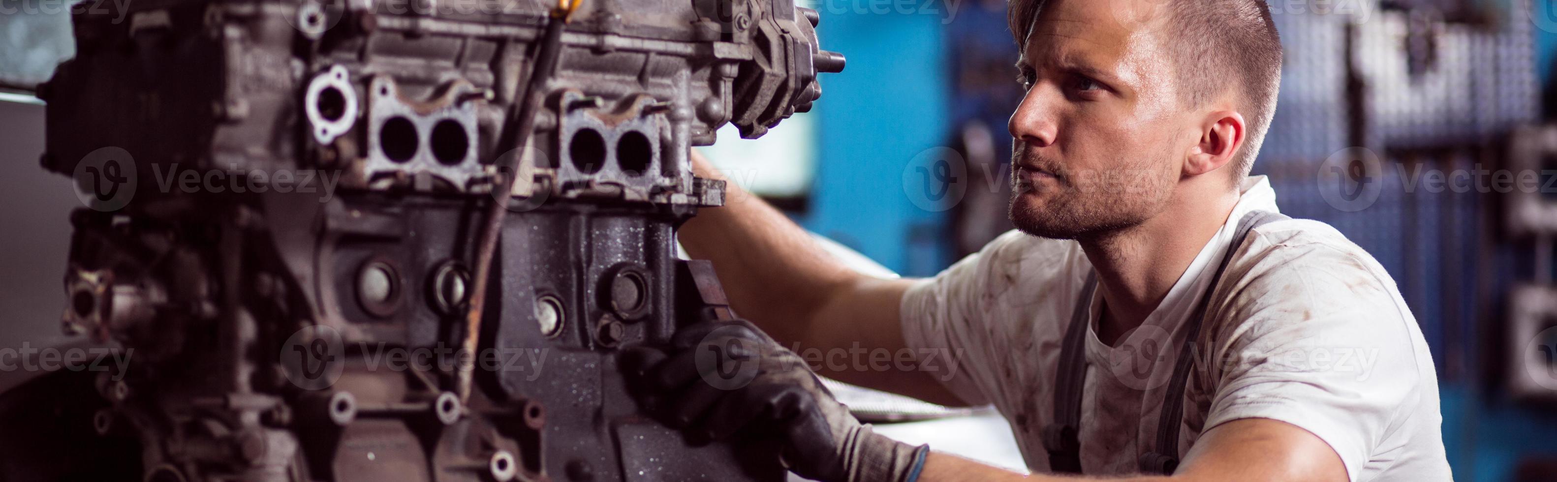 riparatore che ripara il motore di automobile foto