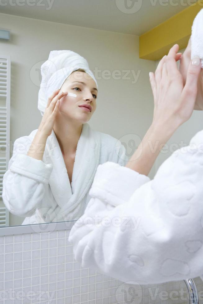 giovane donna che applica la crema di bellezza foto