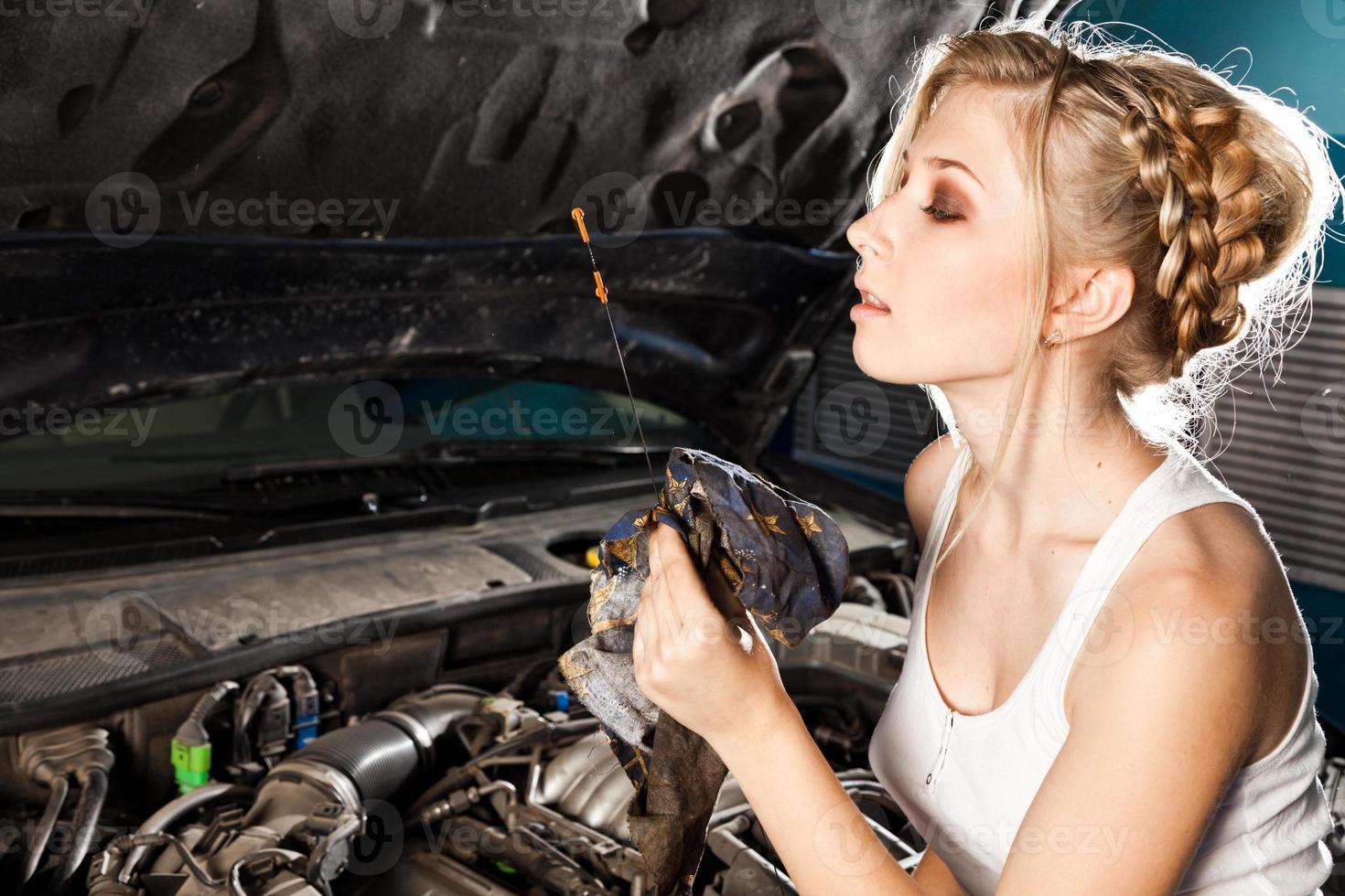 ragazza controlla il livello dell'olio in macchina foto
