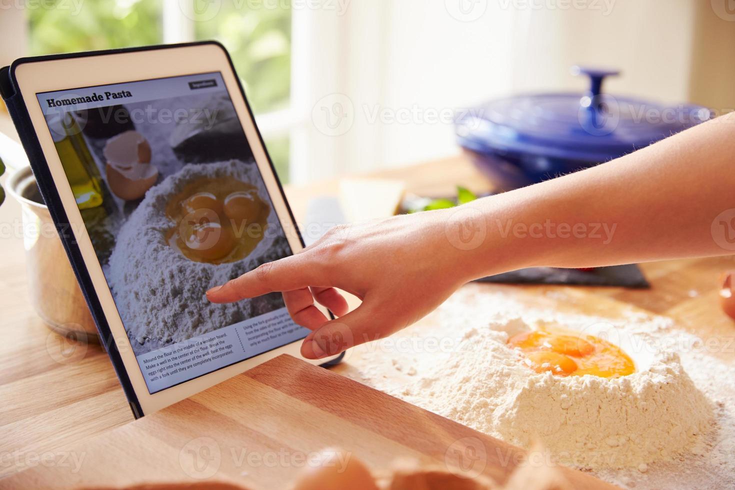 persona che segue la ricetta della pasta utilizzando l'app su tavoletta digitale foto