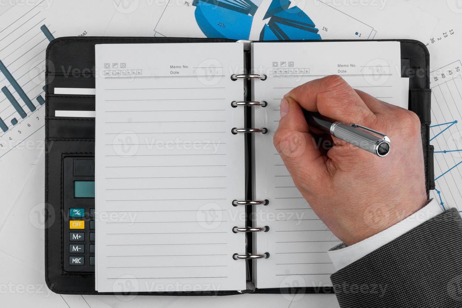 la mano scrive sulla pagina bianca in bianco del taccuino con la penna foto