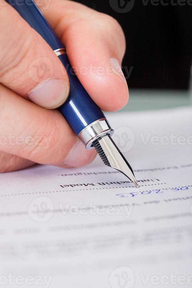 uomo d'affari scrivendo con la penna foto