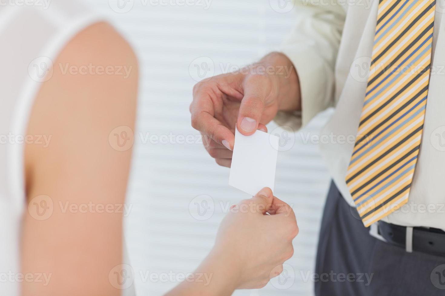 uomo d'affari che passa il suo biglietto da visita foto