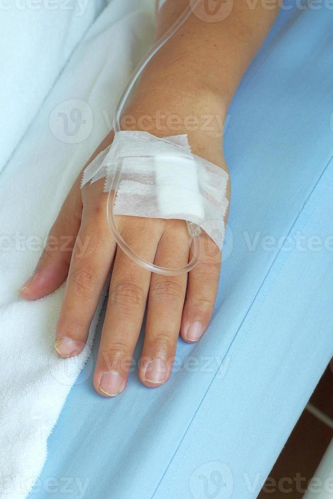 soluzione endovenosa nella mano di un paziente maschio foto