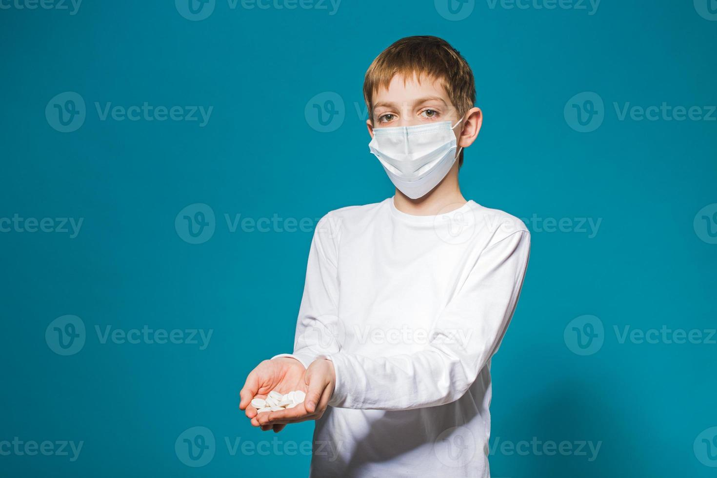 ragazzo in bianco maschera protettiva in possesso di pillole foto