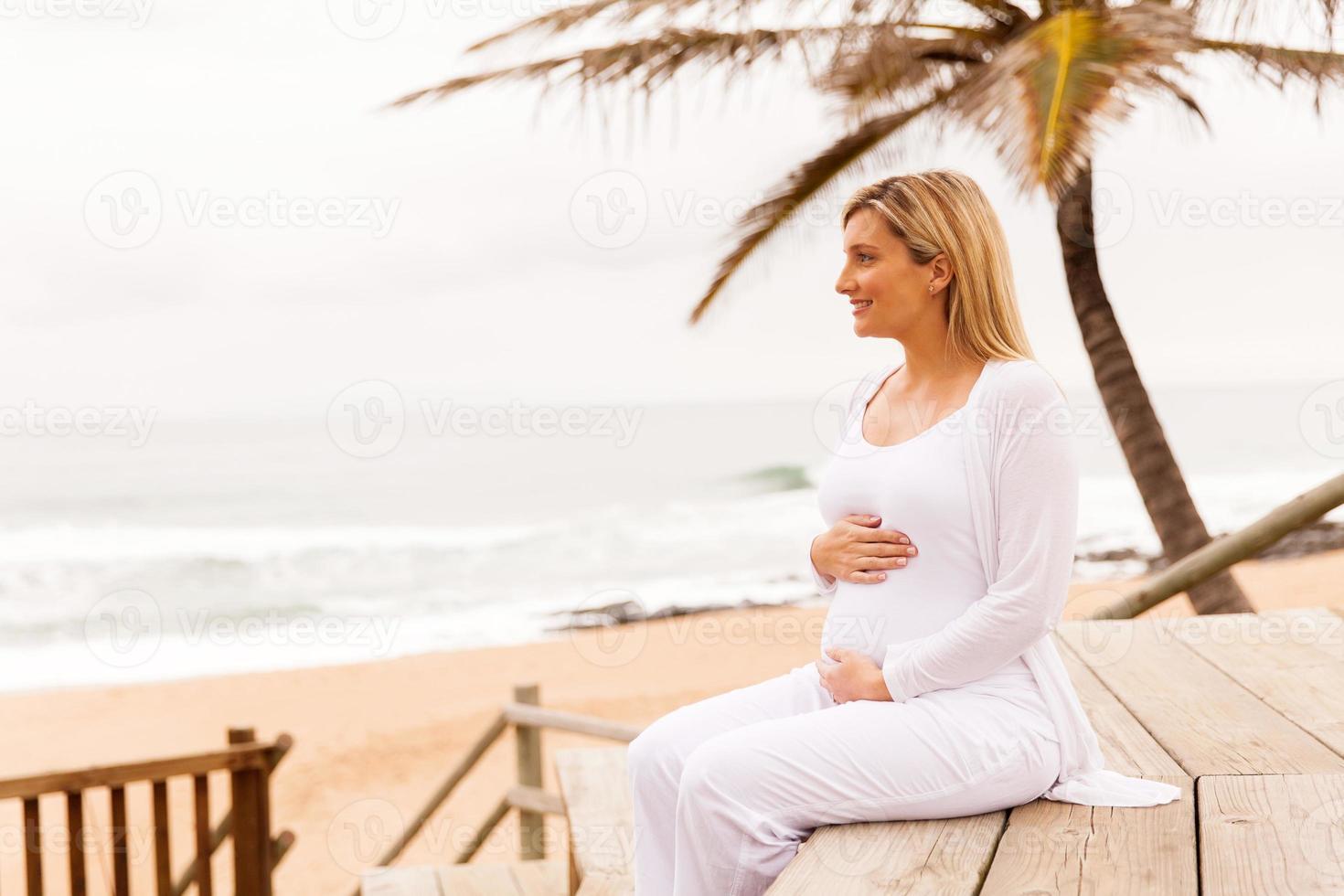 donna incinta sulla spiaggia foto