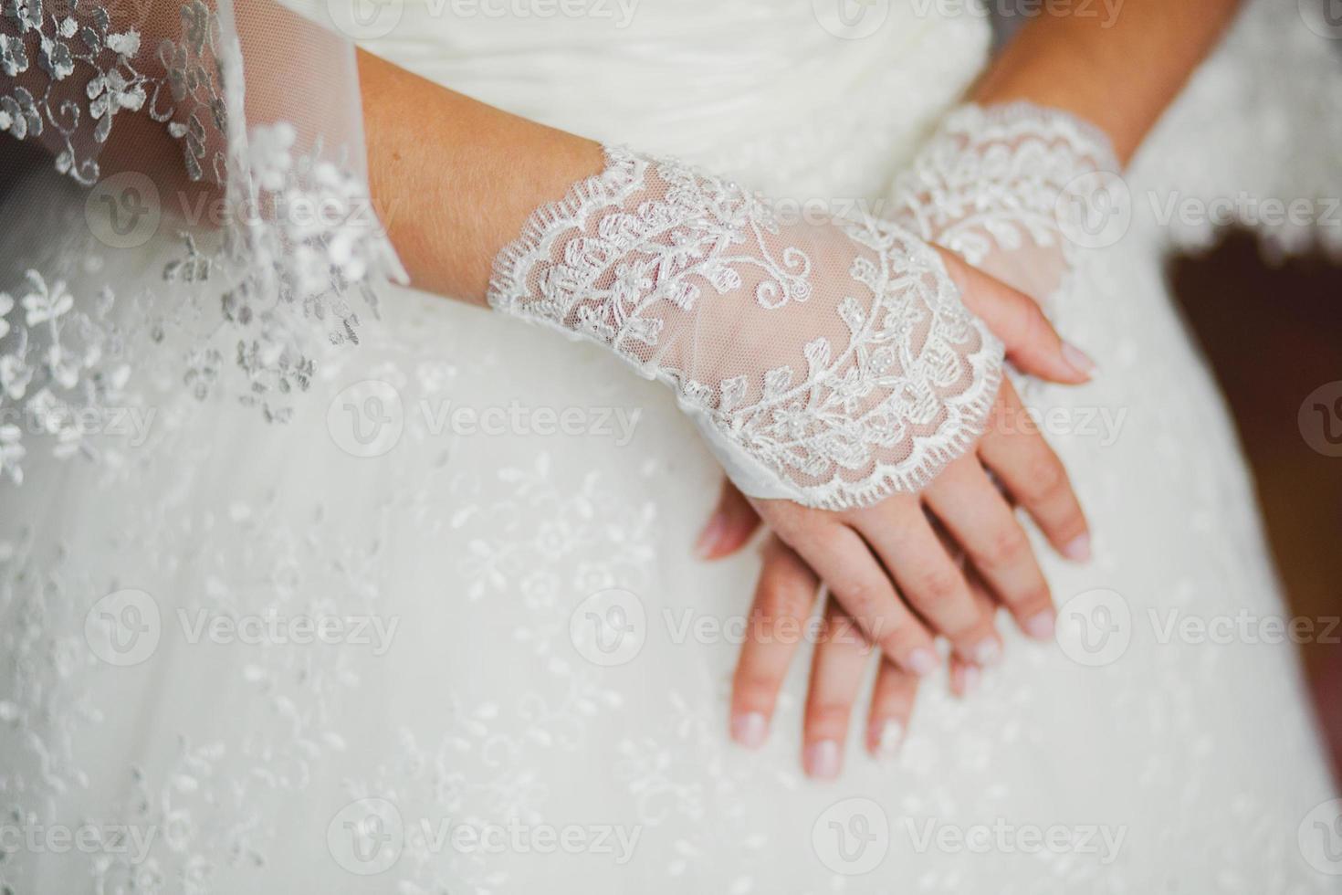 guanti da sposa in pizzo sulle mani della sposa, primo piano foto