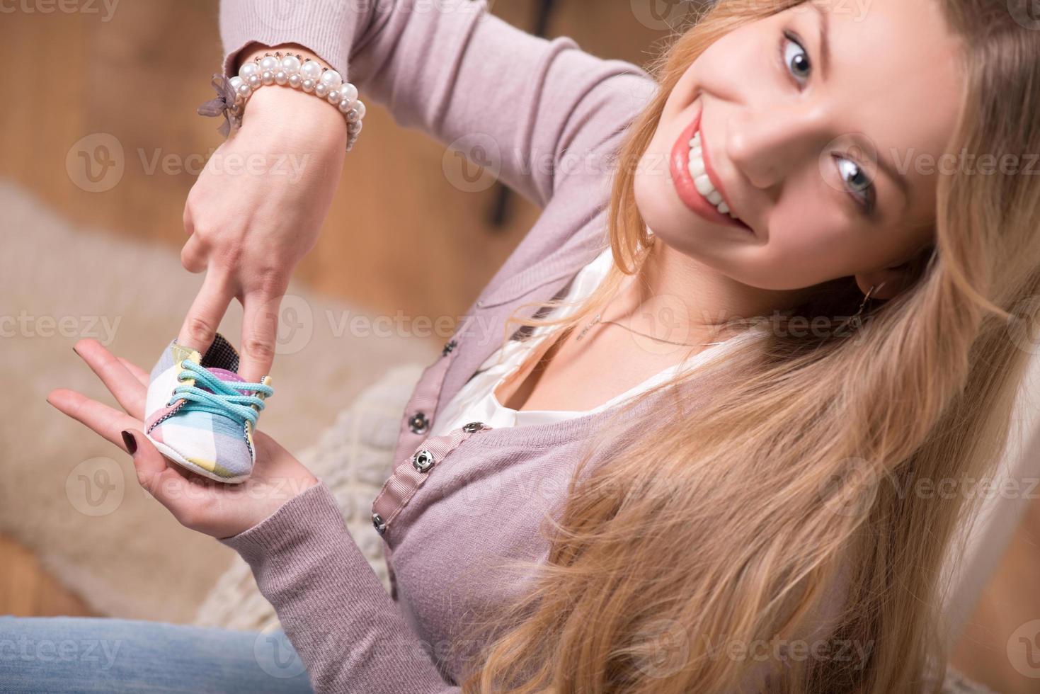 giovane donna attraente che tiene scarpa bambino, colpo interno foto
