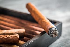 sigaro che brucia con fumo su humidor in legno foto