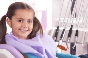 bambina graziosa nella sedia del dentista foto