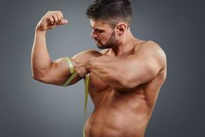 bodybuilder misura bicipiti con metro a nastro foto