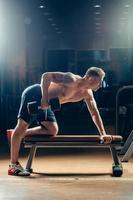 bodybuilder muscolare atleta allenamento indietro con manubri in palestra foto