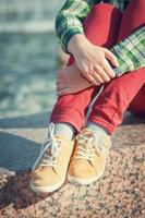 scarpe da ginnastica gialle sulle gambe della ragazza in stile hipster foto