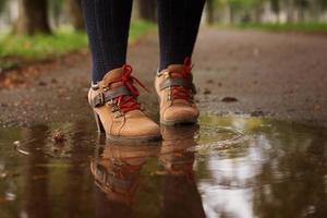 scarpe da donna autunno in una pozzanghera di pavimentazione