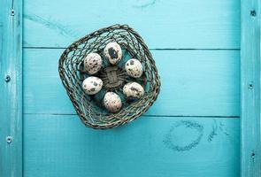 cesto di fieno con uova di quaglia su fondo di legno blu foto