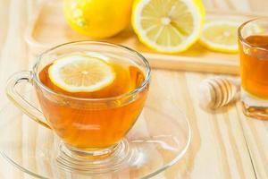 tè con miele e limone su fondo di legno, tonalità calda