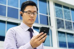 videochiamata parlante dell'uomo d'affari sul cellulare con la cuffia avricolare del bluetooth foto
