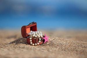 scrigno decorativo con gioielli e stelle marine su una spiaggia foto