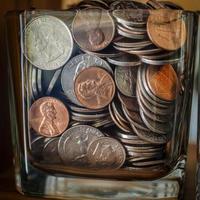 barattolo di risparmio pieno di monete foto