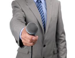 uomo in giacca e cravatta in possesso di un microfono verso la telecamera