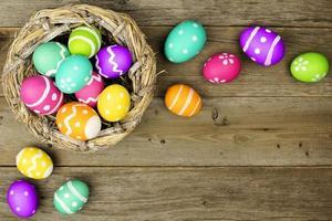 confine dell'uovo di Pasqua con il nido sopra fondo di legno foto