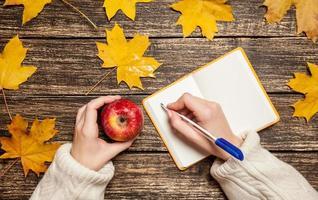 mano femminile che scrive qualcosa sul taccuino e che tiene mela