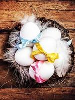 nido di pasqua con uova, nastri e piume bianche foto