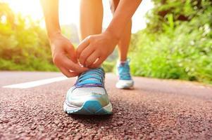 corridore donna legare i lacci delle scarpe sul sentiero foto