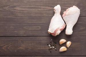 cosce di pollo crudo e pepe, sale, aglio su legno backgr foto